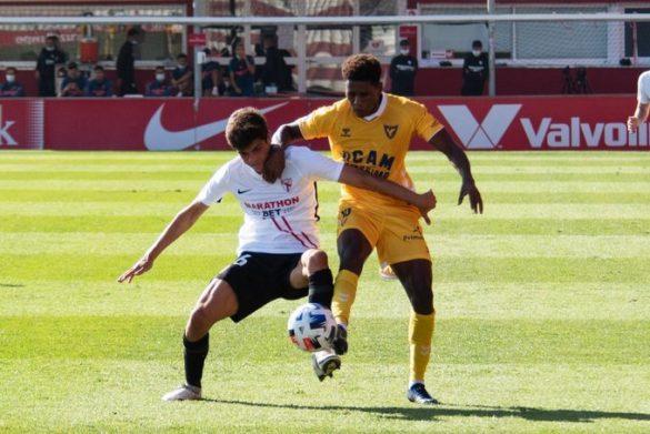 El jugador sevillista Juanlu en la lucha de un balón frente al jugador del UCAM Murcia. Foto: @CanteraSFC